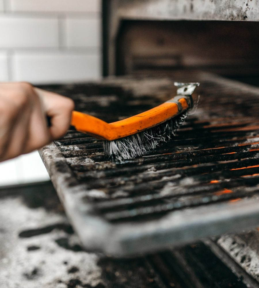 Cook hands with metal brush clean the grill oven